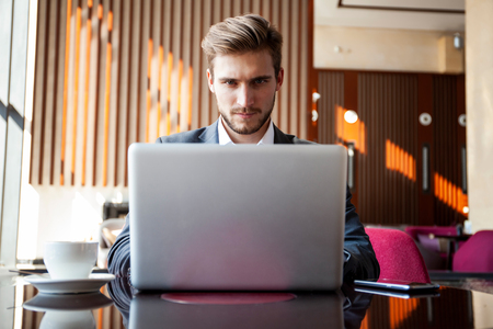 Young businessman working on laptop, sitting in hotel lobby waiting for someone.