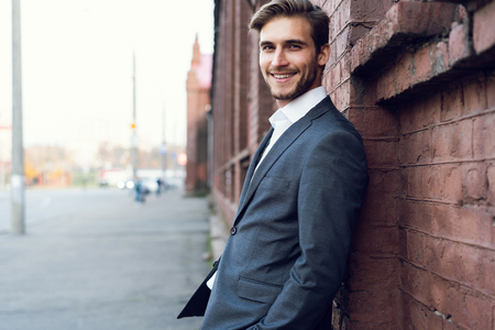 Photo pour Smiling young male manager formal dressed leaning on a wall outdoors. - image libre de droit