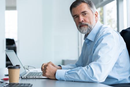 Photo pour Senior businessman working on laptop computer in the office. - image libre de droit