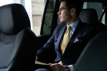 Photo pour Young businessman sitting on back seat of the car, while his chauffeur is driving automobile. - image libre de droit