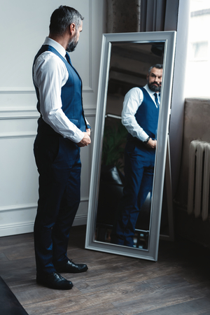 Photo pour Elegant look. Full length of handsome man in full suit adjusting his jacket while standing in front of the mirror indoors. - image libre de droit