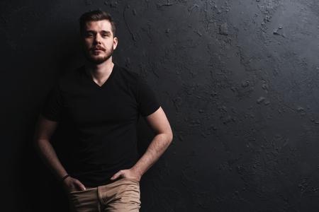 Photo pour young fashion man posing for the camera on black background - image libre de droit