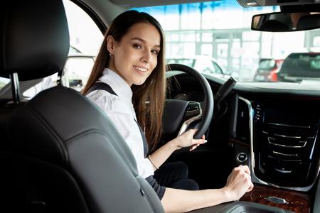 Photo pour Young business woman test drive her new car. - image libre de droit