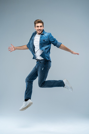 Photo pour Full length portrait of a happy excited beardedman jumping and looking at camera isolated over grey background. - image libre de droit