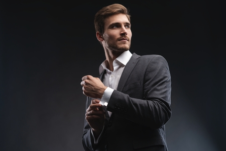 Photo for Perfect to the last detail. Handsome young businessman adjusting his sleeves while standing against gray background. - Royalty Free Image