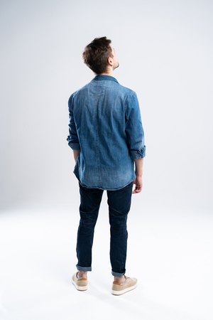 Photo for back view of a casual man standing on white background. - Royalty Free Image