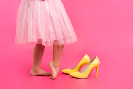 Foto de Little girl in oversized shoes with space for text, closeup on legs isolated on pink. - Imagen libre de derechos