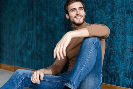 Photo pour young casual fashion man sitting on the floor isolated on dark blue background. - image libre de droit