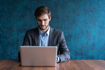 Foto de Happy young businessman using laptop at his office desk. - Imagen libre de derechos