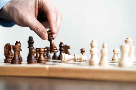 Photo pour hand of businessman moving chess figure in competition success play. strategy, management or leadership concept. - image libre de droit