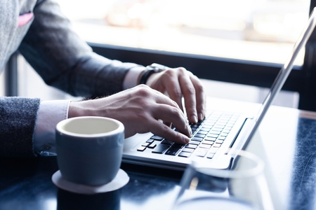 Photo for Young man working on his laptop in a coffee shop, rear view of business man hands busy using laptop at office desk. - Royalty Free Image