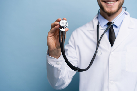 Photo pour Handsome young medic holding a stethoscope, isolated over light blue. - image libre de droit