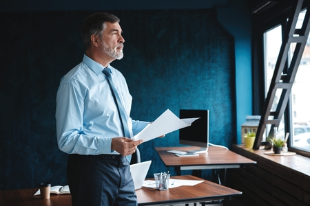 Photo pour Focused concentrated accountant, mature businessman looking at the report, stands in full suit, so successful and intelligent, modern work station. - image libre de droit