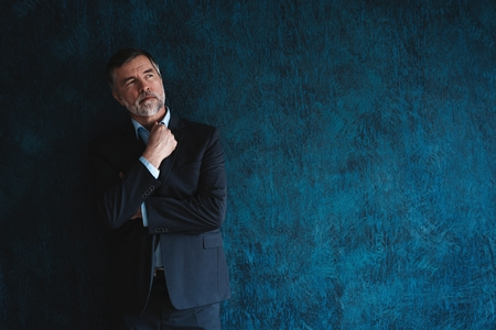 Foto de Serious mature man posing in front of a dark blue background with copy space. - Imagen libre de derechos