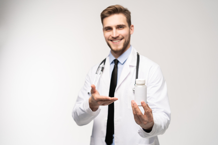 Photo pour Smiling doctor holding a bottle of tablets or pills with a blank white label for treatment of an illness or injury. - image libre de droit