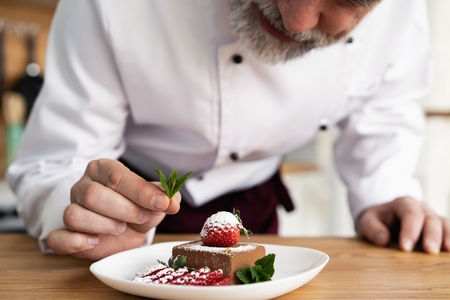 Photo pour Close up pastry chef decoration delicious dessert dish, serving for customers in bakery, garnishing dessert plate in commercial kitchen. - image libre de droit