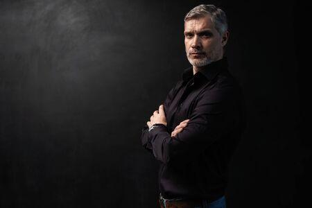Foto de Middle-aged good looking man posing in front of a black background with copy space. - Imagen libre de derechos