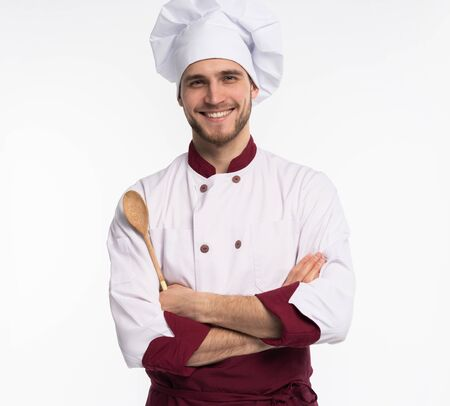 Portrait of positive toothy chef cook in beret, white outfit having tools in crossed arms looking at camera isolated on white background.