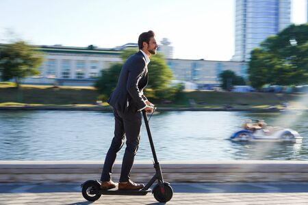 Foto de Young business man in a suit riding an electric scooter on a business meeting. - Imagen libre de derechos