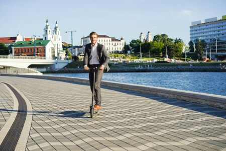 Photo for Young business man in a suit riding an electric scooter on a business meeting. - Royalty Free Image