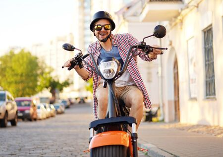 Photo for fashionable young man riding a orange motorbike in the street. - Royalty Free Image