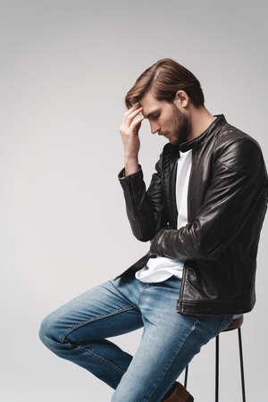 Foto de Fashion man, Handsome serious beauty male model portrait wear leather jacket, sitting on chair over white background. - Imagen libre de derechos