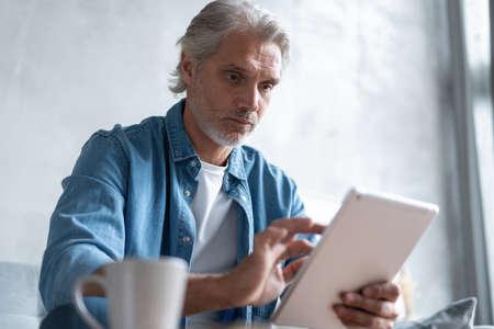 Photo pour Handsome businessman working on tablet from home. - image libre de droit