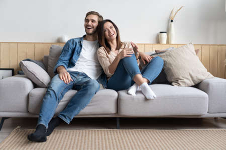 Photo pour Happy young Caucasian couple relax on cozy sofa at home hugging look in distance dreaming together - image libre de droit