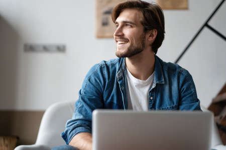 Foto de Successful entrepreneur smiling in satisfaction as he checks information on his laptop computer while working - Imagen libre de derechos