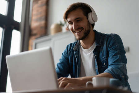 Photo for Man Using Laptop Wearing Headphones Relaxing Sitting On Sofa At Home. - Royalty Free Image