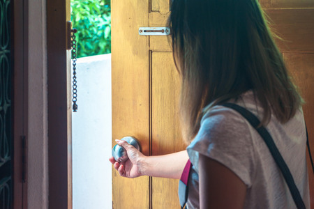 Asian woman grabbing door knob opening brown wooden door.