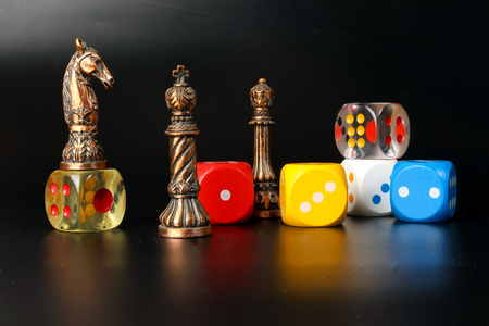 Foto de Colourful playing gaming dice transparent metal chess pieces on black background - Imagen libre de derechos