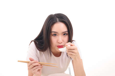 Photo for Beautiful young south east Asian woman holding chinese empty chopstick soup spoon bowl utensil pretend acting posing see eat taste feed offer satisfaction yummy white background happy blow cool - Royalty Free Image