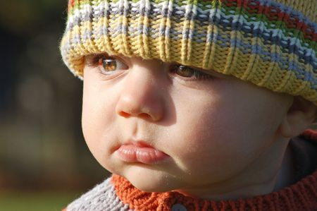 Close up shot of a young boy outdoors in a sweater and wool cap
