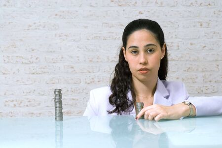 An isolated shot of young female bank teller sitting behind a pile of coins.  The woman has a serious/ominous expression on her face.