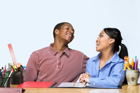 Two Teens are are seated at a desk  laughing, and smiling at each other. There are  pens, pencils, folders and paper on the desk. Horizontally framed photograph