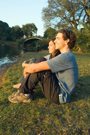 Couple sitting and talking by a pond. They are staring ahead and smiling. There is a bridge in the background. Vertically framed photograph