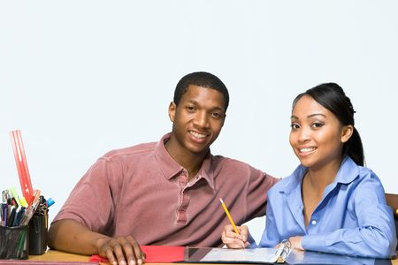 Two Teens are are seated at a desk taking notes and smiling. There are pencils, folders, and paper on the desk. Horizontally framed photgraph