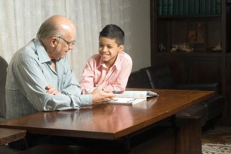 Grandfather and grandson are sitting at the table reading a book. Grandfather smiles as he reads the book to his grateful grandson. This is a horizontally framed photo.