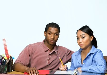 Two Teens are are seated at a desk taking notes and looking serious. There are pencils, folders, and paper on the desk. Horizontally framed photgraph