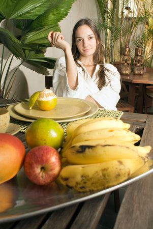 Woman smiles as she has breakfast. There are many fruits on the table. Vertically framed photograph.