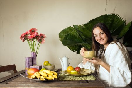 Woman smiles as she has breakfast. She is holding a tea cup. There are many fruits on the table. Horizontally framed photograph.