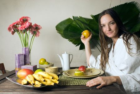 Woman smiles as she has breakfast. She is holding an orange. There are many fruits on the table. Horizontally framed photograph.