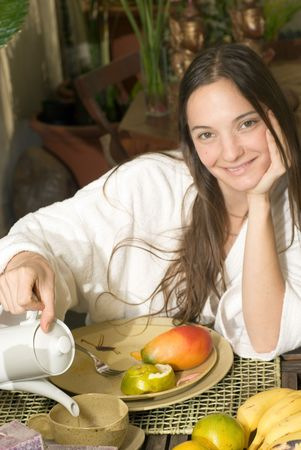 Woman smiles as she has breakfast. There is fruit on her plate and she is pouring tea. Vertically framed photograph.