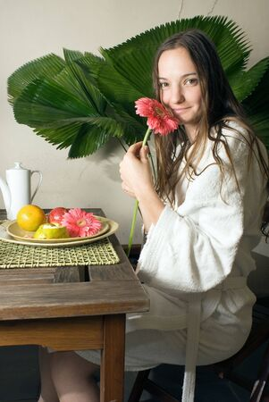 Woman smells a pink daisy as she is having fruit for breakfast. There is a large plant behind her. Vertically framed photograph.