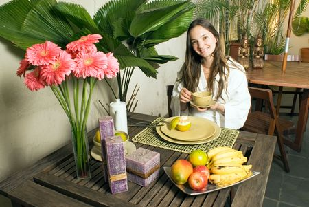 Woman smiles as she has breakfast. There are fruit, candles, and flowers on the table. Horizontally framed photograph.