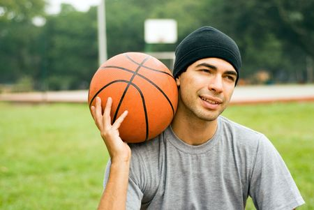 Man wearing a hat is sitting down in a park holding a basketball.  There is a basketball court behind him.  He appears to be amused.  Horizontally framed shot.