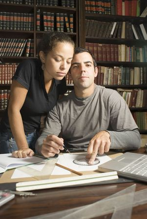 Couple studies in library. There are books and tools on the table and they are leaning against eachother. Vertically framed photo.