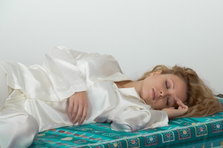 Young woman-girl in pajamas asleep lying on the soft mattress of his bed