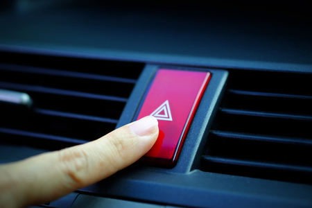 Close up of Finger pressing emergency button in car, selective focus and vignette effect design.
